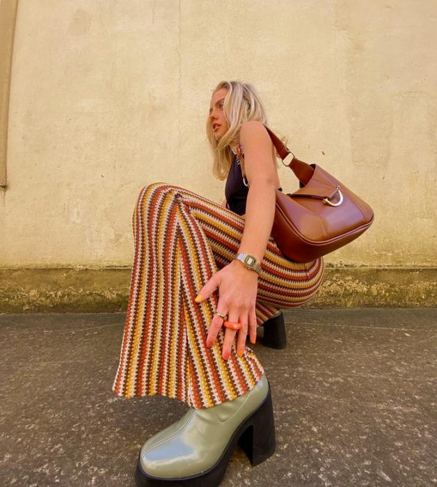 chica rubia con top negro sin mangas, pantalones acampanados de rayas de colores rojas, amarillas, naranjas, botines beige de plataforma negra y bolso pequeño café de piel
