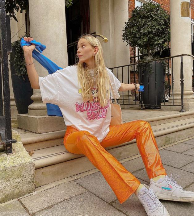 chica rubia con camiseta blanca oversized, pantalones naranja brillantes acampanados, tenis blancos y suéter azul