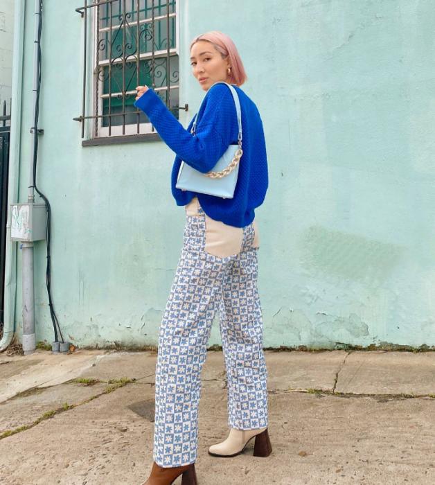 chica de cabello rubio corto con suéter azul brillante, pantalón blanco con azul, botines beige con café y bolso celeste