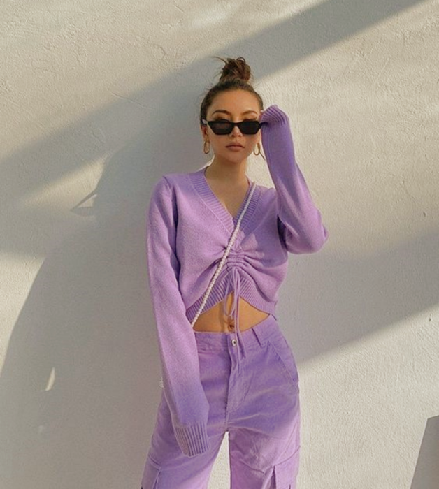 chica de cabello oscuro con crop top de manga larga morado lila, pantalón morado pastel