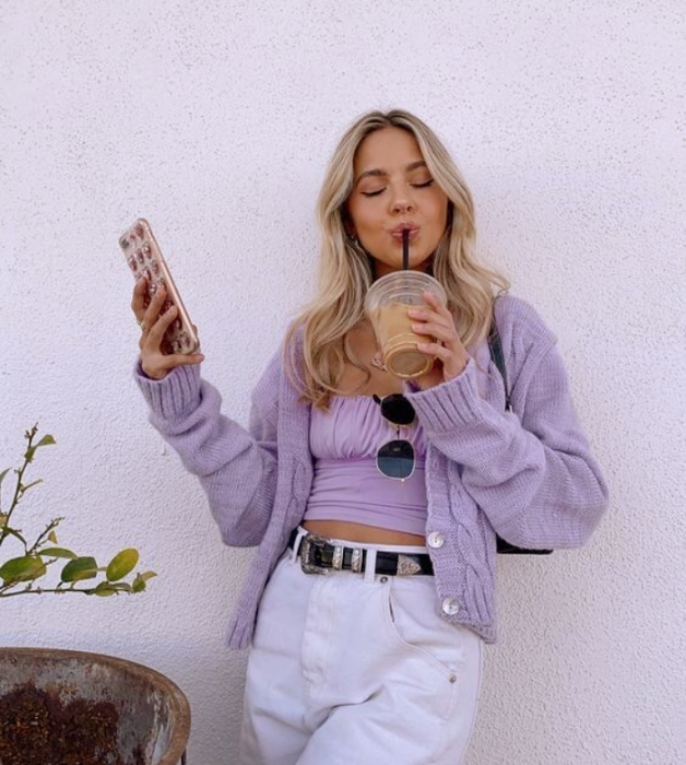 blonde girl in lilac knitted cardigan, lilac strappy crop top, baggy white pants and black leather belt