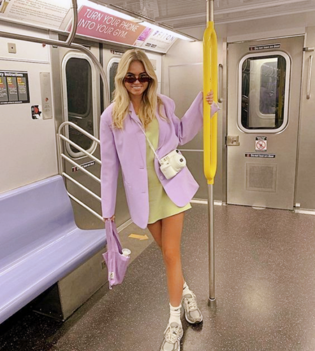 blonde girl with black sunglasses, lilac blazer, light green dress, white tennis shoes and lilac small bag