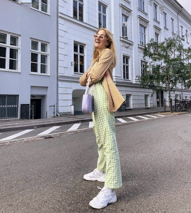 blonde girl with beige sunglasses, yellow blazer with white squares, light green pants, white tennis shoes, lilac bag