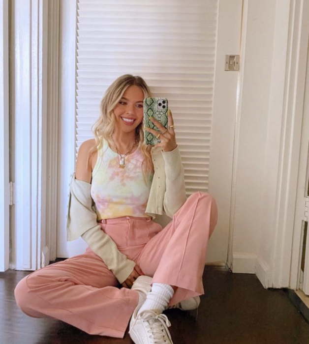 blonde girl wearing white tank top with pastel pink flared pastel pink pants white tennis shoes and light green cardigan