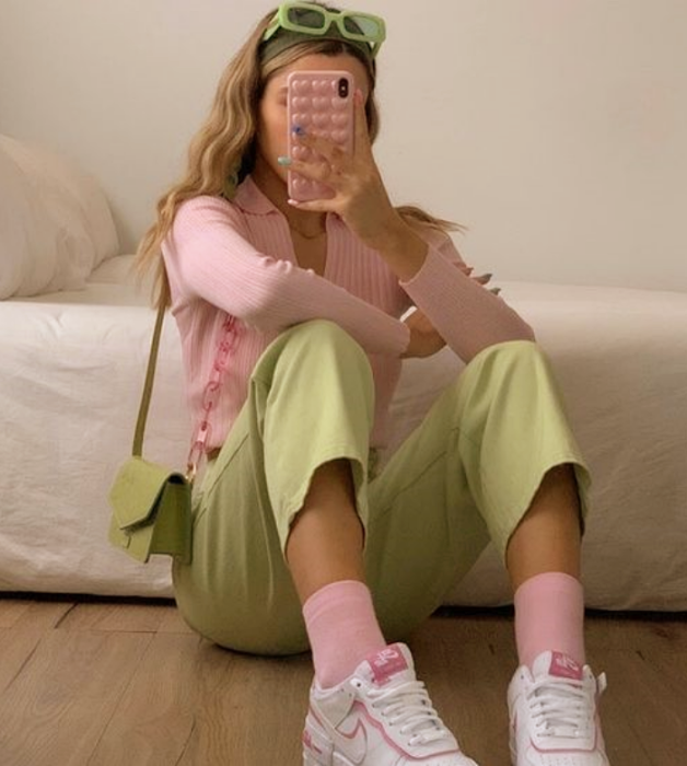chica rubia usando lentes de sol verdes, cárdigan top rosa claro, pantalones verde pastel cortos, calcetas rosas pastel, bolso verde claro de piel