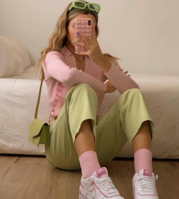 blonde girl wearing green sunglasses, light pink top cardigan, short pastel green pants, pastel pink socks, light green fur bag