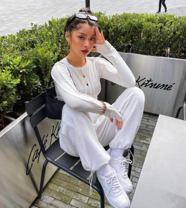 chica de cabello oscuro usando lentes de sol, top blanco de manga larga, pants blancos oversized, tenis blancos