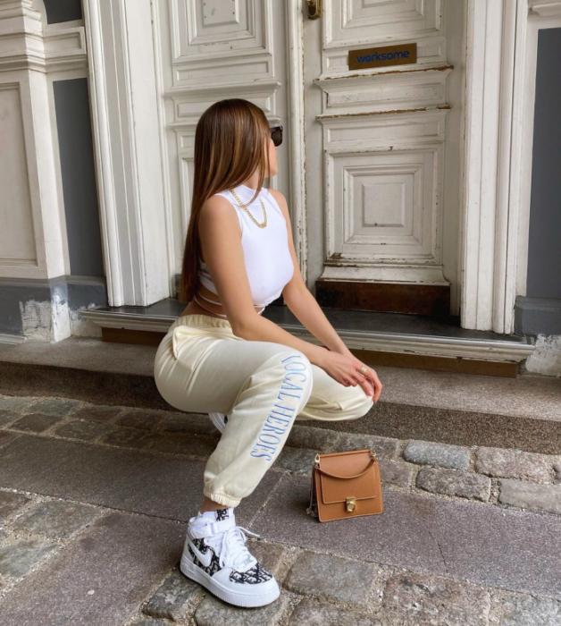 chica de cabello claro usando un top blanco de manga corta, pants beige holgados, tenis blancos con negro, bolso café claro pequeño