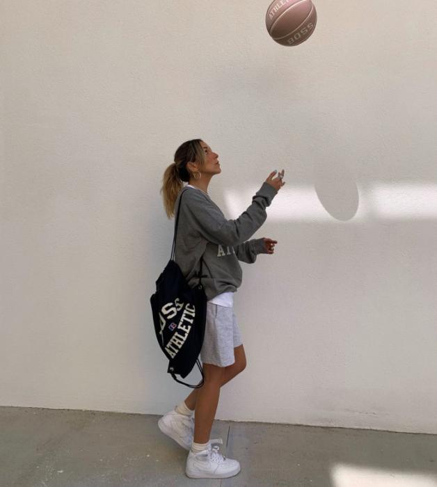 chica de cabello claro usando una sudadera gris oversized, shorts grises claros, tenis blancos, bolso tote bag negro con letras blancas