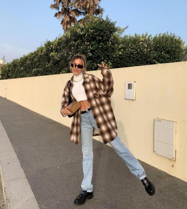 chica de cabello claro usando lentes de sol, crop top blanco de manga corta, camisa de cuadros cafés con beige, jeans holgados rectos, zapatos de cuero tipo mocasines