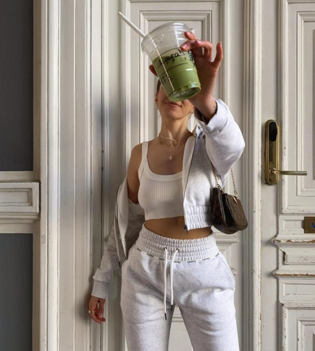 chica usando un crop top blanco de tirantes, sudadera blanca de zipper, pants blancos, bolso pequeño café