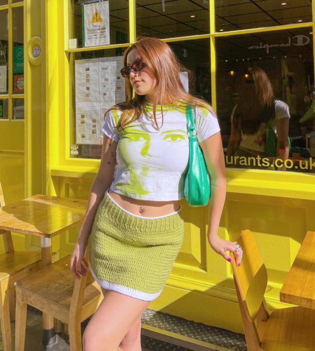 chica de cabello claro usando lentes de sol, camiseta blanca, minifalda amarilla con lineas blancas, bolso verde brillante de mano