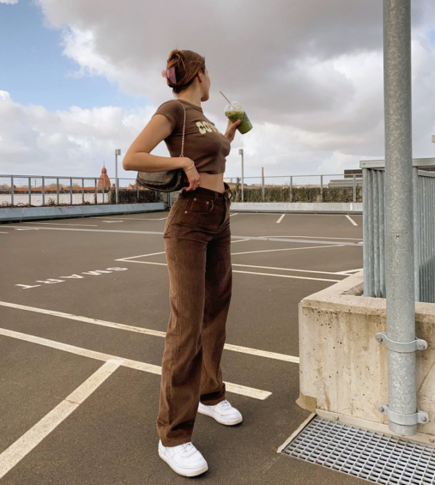 chica de cabello castaño usando un crop top café, cubrebocas negro, camisa de cuadros oversized café con negro y beige, jeans ajustados a la cintura