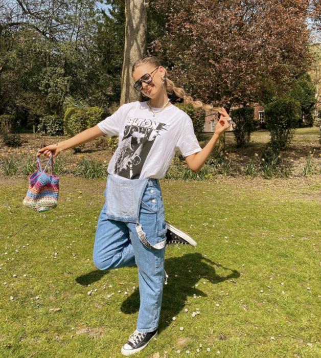 chica rubia con lentes de sol, camiseta blanca oversized, overol de mezclilla holgado, tenis deportivos converse negros