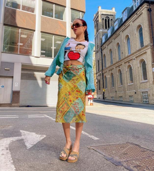 chica de cabello oscuro usando lentes de sol, camiseta gráfica blanca con corazón rojo, falda amarilla con verde y azul, sandalias de plataforma café