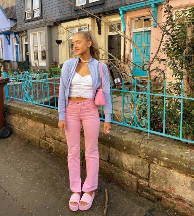 chica rubia con top blanco corto, pantalones rosas rectos, sandalias rosas de plataforma, cárdigan azul celeste, bolso rosa pequeño