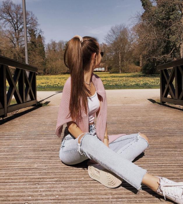 chica de cabello castaño usando un top blanco, cárdigan rosa claro, jeans rotos claros, tenis blancos