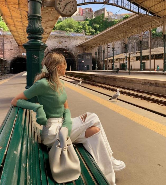 chica rubia con top verde tejido de manga larga, jeans blancos rotos, tenis blancos, bolso blanco grande cuero