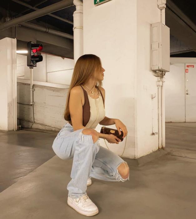 chica de cabello claro usando un top beige con café sin mangas, jeans holgados rotos, tenis blancos