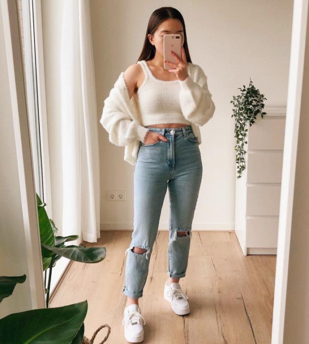chica de cabello oscuro usando un crop top blanco, cárdigan blanco tejido, jeans ajustados rotos, tenis blancos