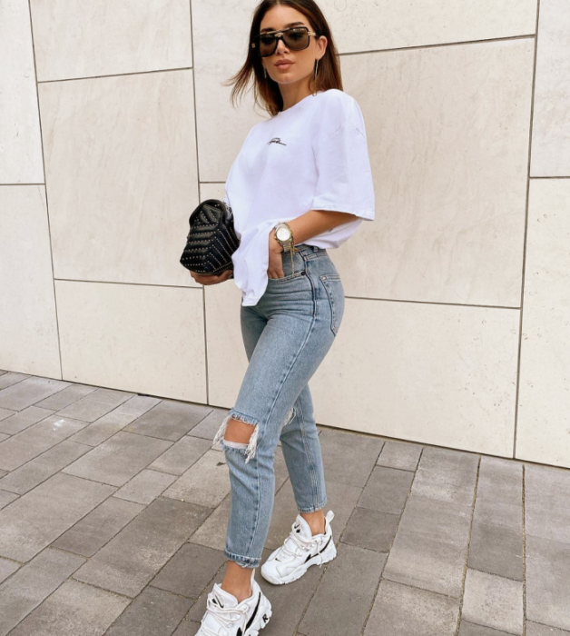 chica de cabello oscuro corto usando lentes de sol, camiseta blanca holgada, tenis blancos, jeans ajustados rotos, bolso negro de mano