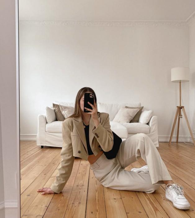 chica de cabello claro usando un top negro, blazer corto beige, pantalones blancos, tenis blancos, bolso negro de cuero