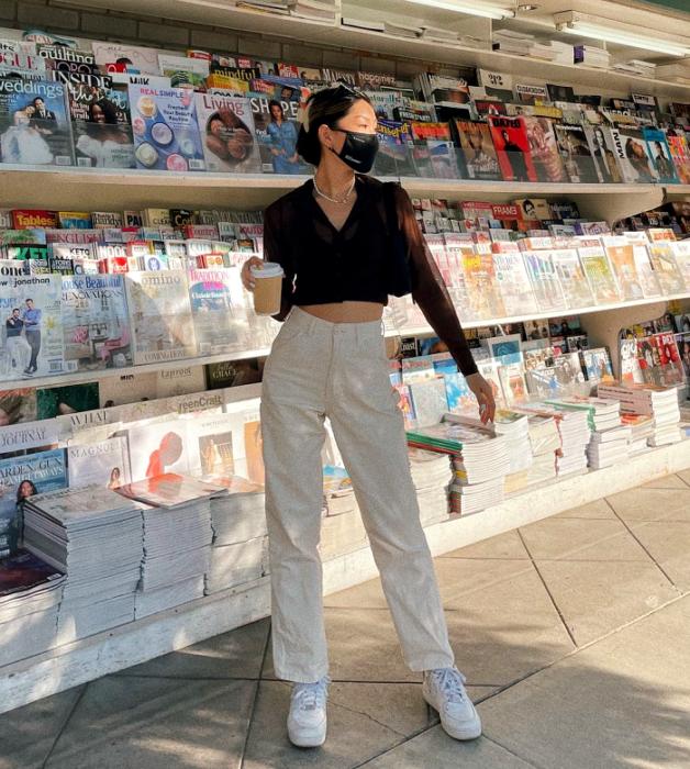 chica de cabello negro usado un crop top café de manga larga, pantalones blancos, tenis blancos