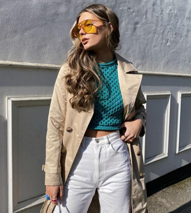 chica de cabello claro usando lentes de sol amarillos, top verde corto, abrigo beige claro