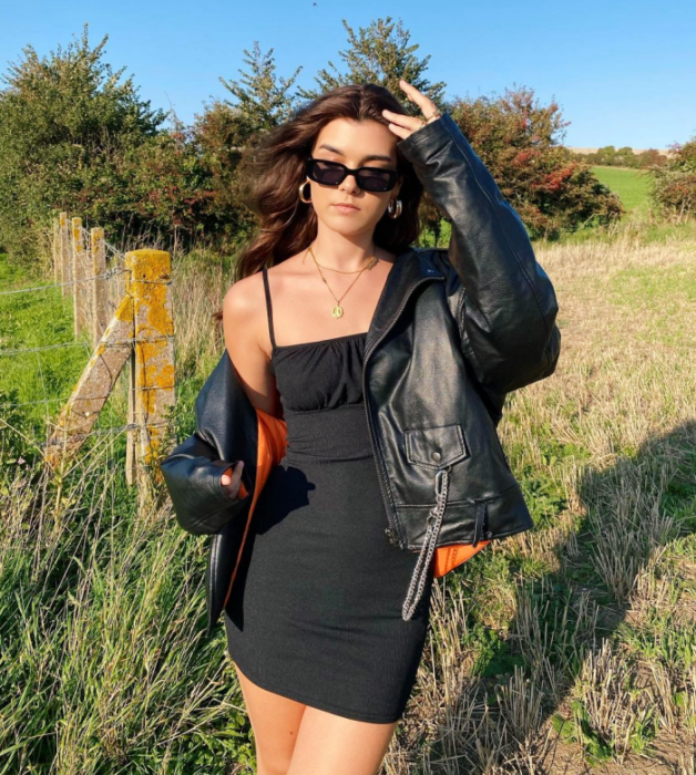 brown haired girl wearing sunglasses, black bodycon dress with straps, leather jacket with orange lining