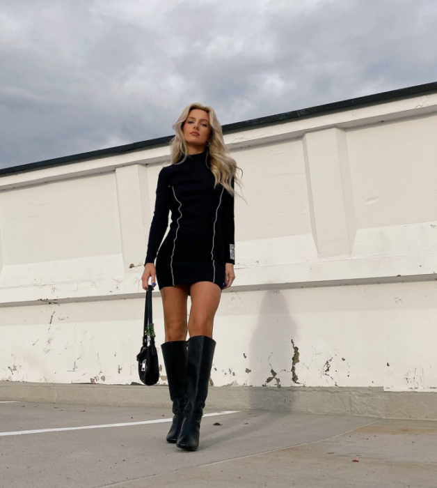 blonde girl in long sleeve tight black bodysuit and short shorts, long leather boots, black handbag