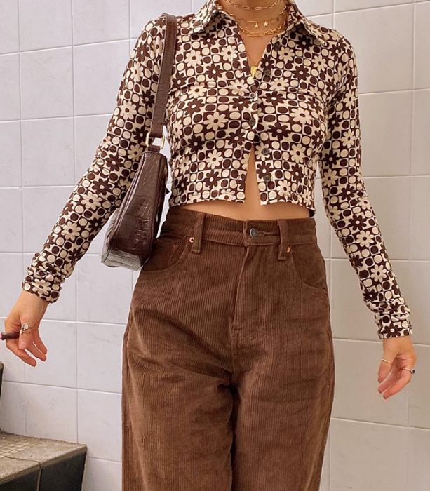 girl in white long-sleeved short button-down shirt, beige with coffee, brown baggy corduroy pants, leather coffee bag