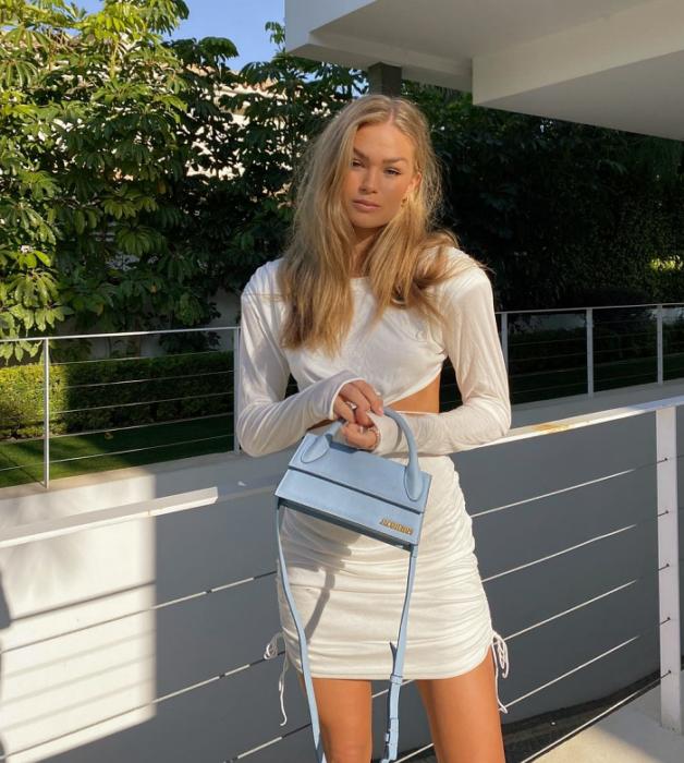 chica rubia con vestido blanco ajustado con apertura en los lados, bolso pequeño celeste de cuero