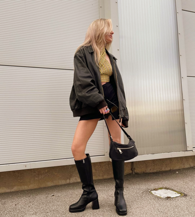 chica rubia con top amarillo con verde, chamarra de cuero, minifalda negra, botas largas de cuero, bolso pequeño negro de cuero