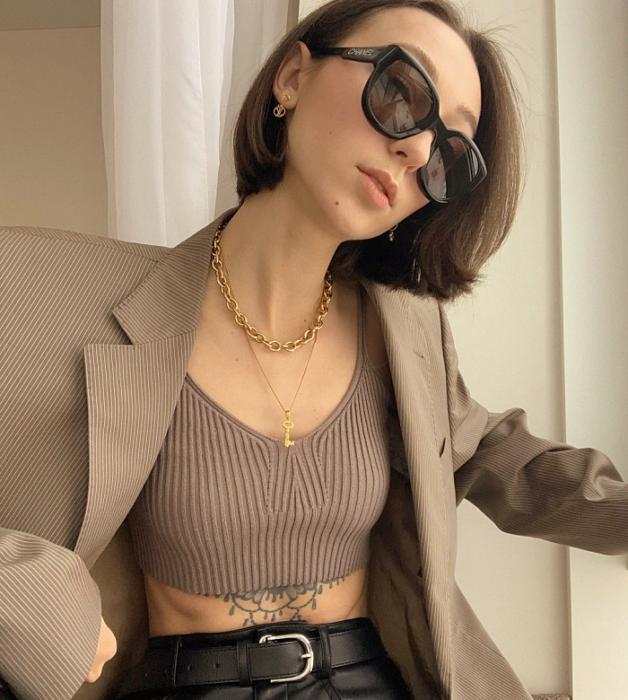 chica de cabello castaño corto usando lentes de sol, crop top café tejido, saco blazer café claro holgado, pantalones de cuero ajustados a la cintura