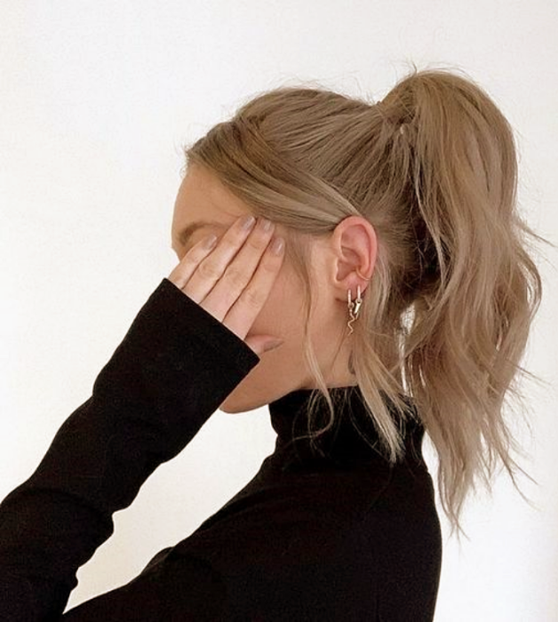 blonde girl with high bun, black top with high neck and long sleeves
