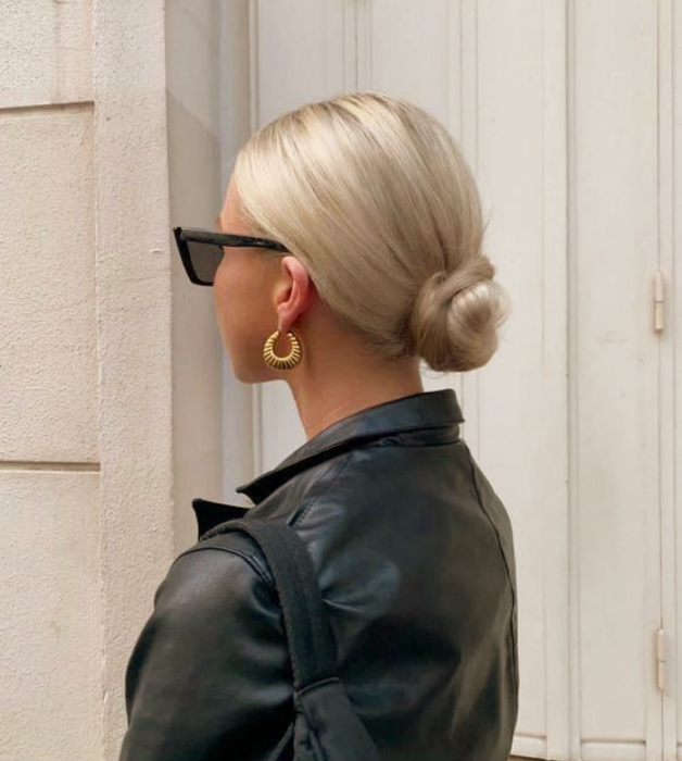 Platinum haired girl in low bun, black sunglasses and black leather jacket