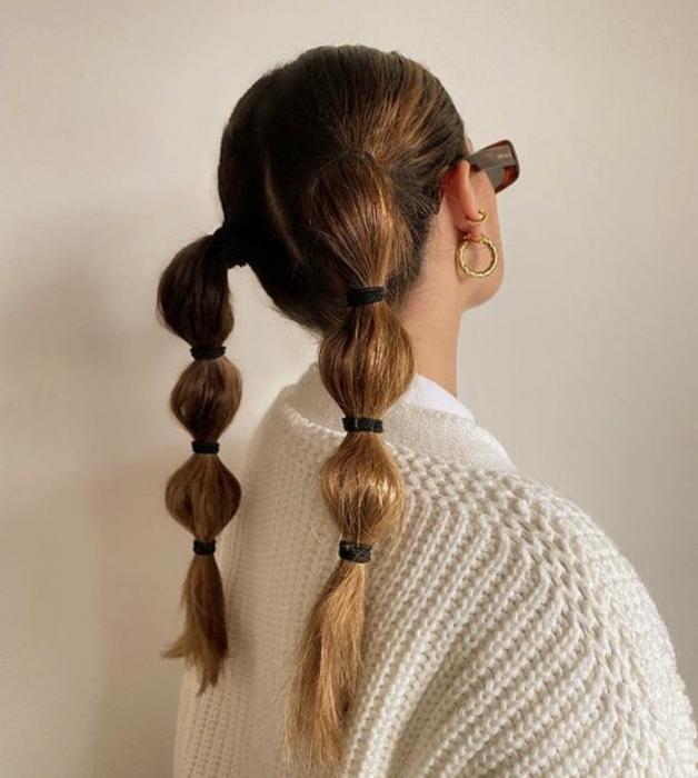 chica de cabello claro largo usando coletas abombadas con suéter blanco y lentes de sol negros