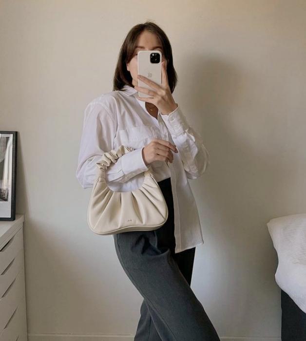 chica de cabello castaño corto usando una camisa blanca de vestir, pantalones de mezclilla oscuros a la cintura y bolso de mano blanco de piel