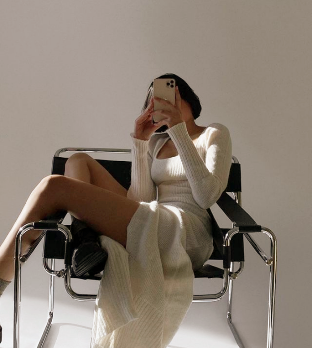 chica de cabello corto castaño con vestido beige ajustado de manga larga abierto de la falda, botas de cuero largas