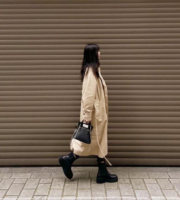 chica de cabello castaño largo usando un abrigo largo beige, botines negros de cuero, bolso negro de cuero