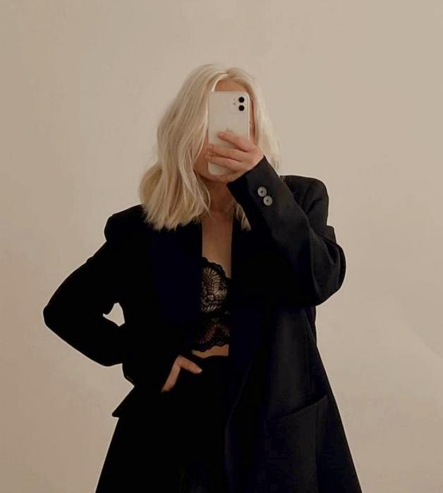 chica de cabello rubio platinado usando un bralette negro de encaje, saco negro y pantalones negros de vestir