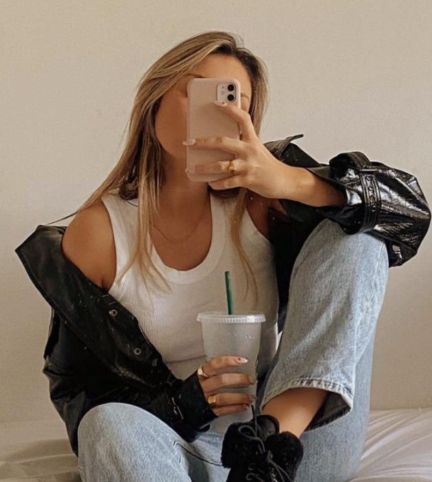 chica rubia usando un top blanco de tirantes, chamarra de cuero, jeans ajustados, botines negros