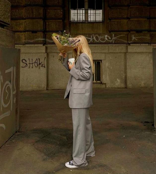 chica rubia usando un traje gris de dos piezas con tenis converse negros y flores en la mano