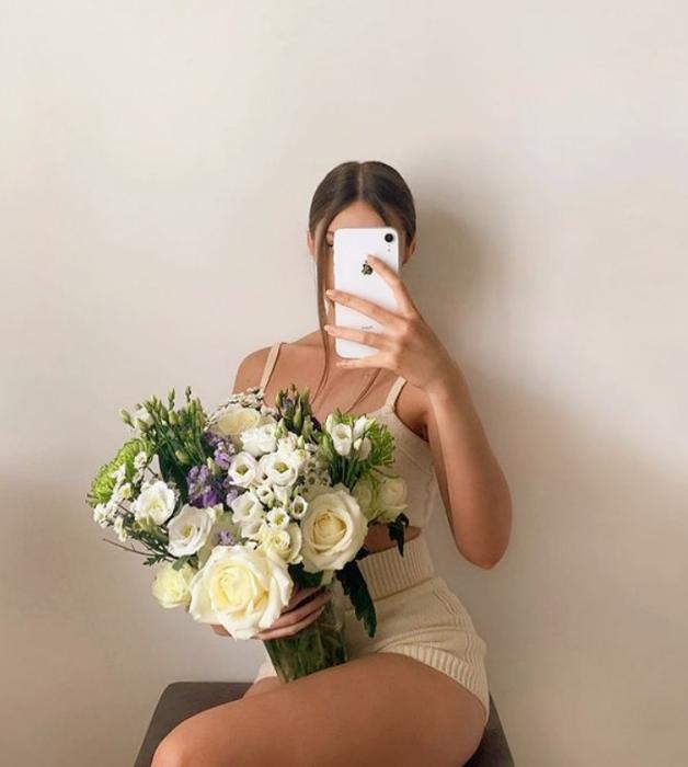 chica de cabello castaño usando un top de tirantes tejido beige, shorts tejidos beige y un florero en la mano