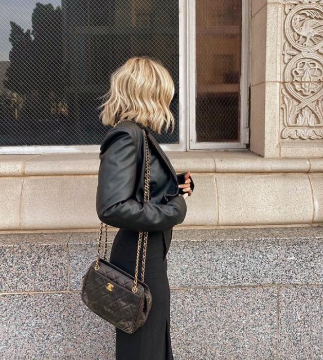 chica rubia de cabello corto usando una chaqueta de cuero, pantalones negros y bolso negro de mano