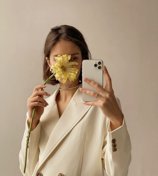 chica de cabello castaño corto usando un blazer saco beige grande con flor amarilla en la mano cubriéndole el rostro
