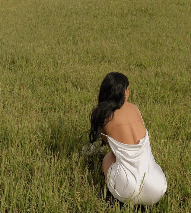 chica de cabello castaño largo usando un vestido de satén color beige claro