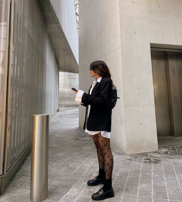 chica de cabello castaño usando una camisa blanca de vestir, blazer negro oversized, medias negras de red, botines negros de cuero