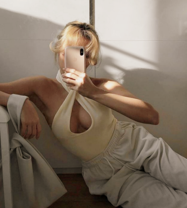 chica rubia usando un top beige de tirantes cruzados con escote de ovalo, pants blancos holgados