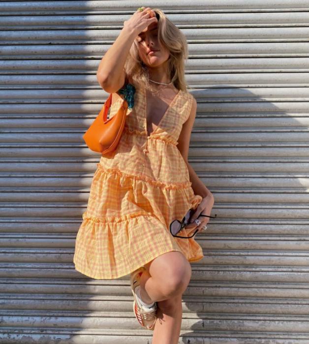 chica rubia con vestido naranja holgado con vuelo, bolso naranja brillante de cuero pequeño y tenis blancos con naranja